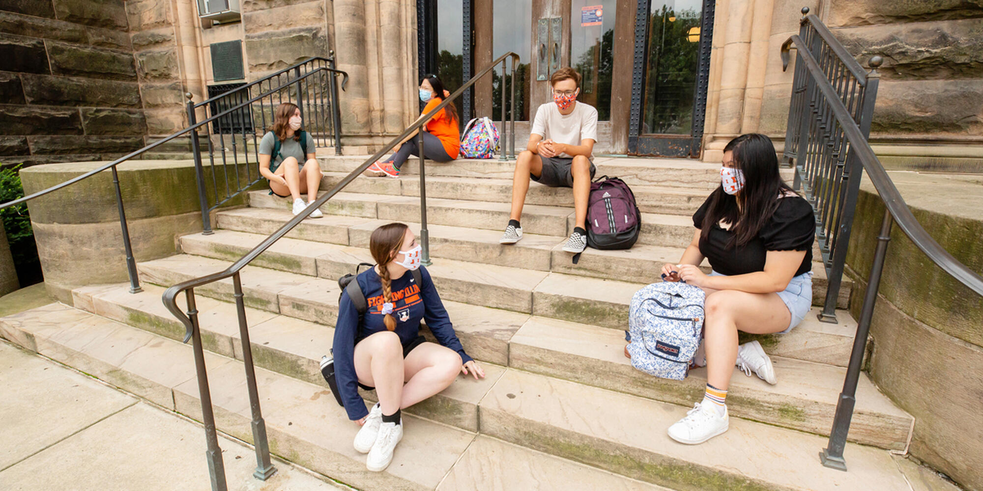 students sitting on outside steps wearing masks as part of the COVID-19 response